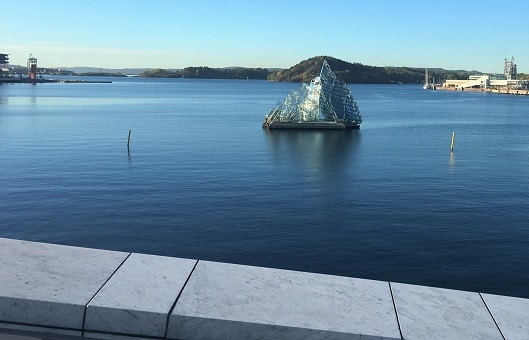 "Oslo Layover - ""She Lies"" made from glass and stainless steel, depicts an iceberg floating in the Harbor."