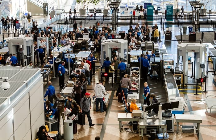 People waiting in line at TSA checkpoint security at airport